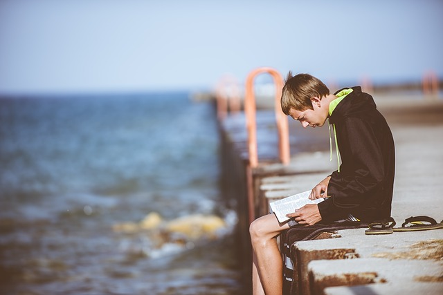 Boy reading on dock